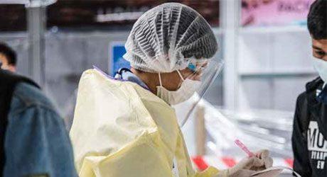 foto de uma pessoa com máscara, faceshield, touca e avental fazendo anotações em um bloco
